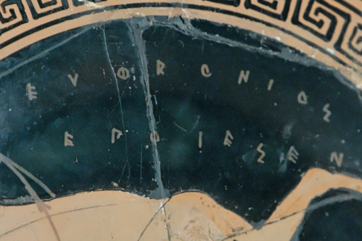 """Euphronios' signature (ΕΥΦΡΟΝΙΟΣ ΕΠΟΙΕΣΕΝ) as potter, rotated 90° anticlockwise, detail from a scene representing a rider. Tondo from an Attic red-figure kylix, ca. 500–490 BC. From Vulci."" (Wikimedia Caption, Wikimedia Image)."
