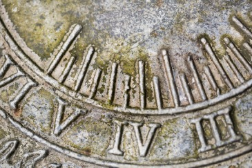 Close up of Roman numerals on weathered  sundial