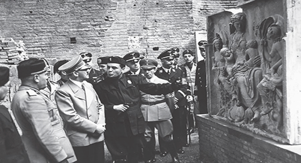 "Album of ""The Führer's Trip to Italy"": Adolf Hitler and Benito Mussolini following a guide showing the authorities a fragment depicting Saturnia Tellus, a detail of the Ara Pacis. Henrich Himmler, Joseph Goebbels and Joachim von Ribbentrop are visible in the group. The work was reconstructed in 1938 in celebration of bi-millenium anniversary of Augustus. © Alinari Archives, Florence"
